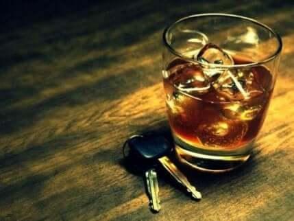 Bilnøkler som ligger ved siden av et glass whisky