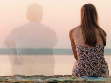 En kvinne som sitter på stranden med en mann som svinner hen.