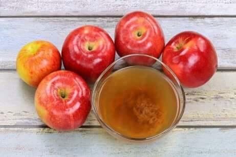 Epler som ligger rundt et glass med eplecidereddik