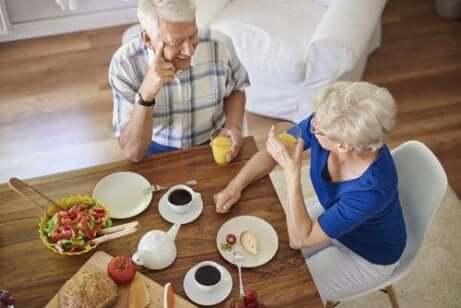 Et eldre par som snakker sammen over frokost