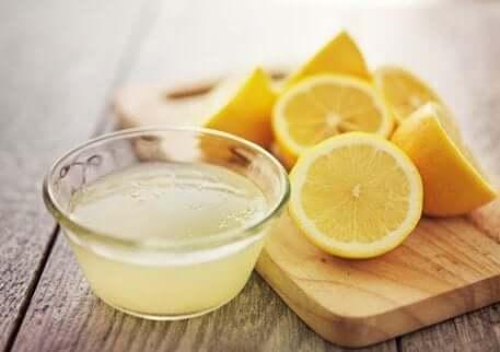 Sitronsaft i en bolle med sitroner liggende i bakgrunnen