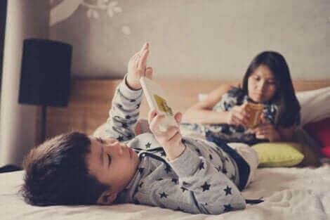 To barn som stirrer på smarttelefoner.
