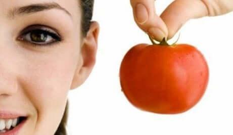 en kvinne som holder en tomat
