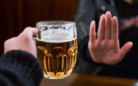 en person som sier nei til et glass øl