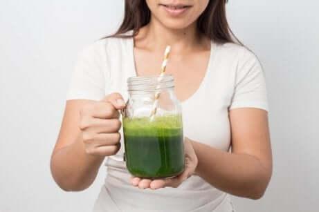 Kvinne holder et glass agurkjuice