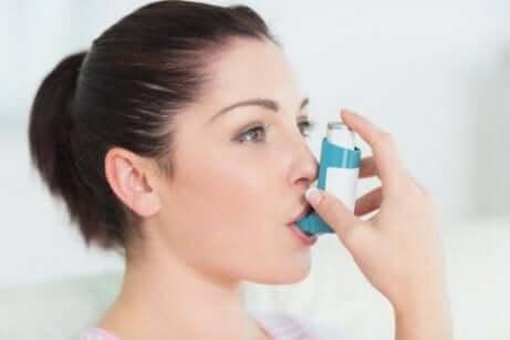 kvinne som bruker en astmainhalator