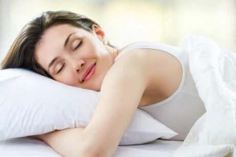 Hvordan få en god natts søvn: kvinne som sover fredelig på en pute