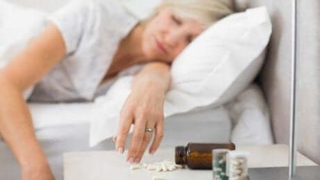kvinne som sover ved siden av sovepiller