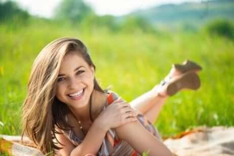 lykkelig kvinne ligger på en eng