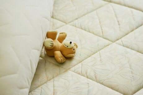 En bamse som ligger på en madrass