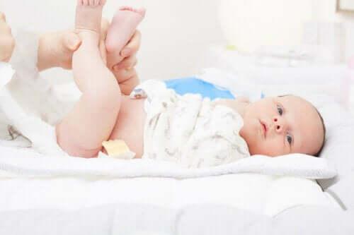 En person som bytter bleie på babyen.
