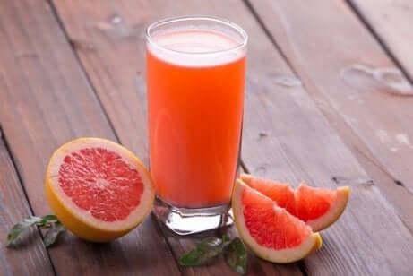 Et glass grapefruktjuice ved siden av en grapefrukt.