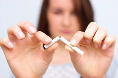 en kvinne som knekker en sigarett i to