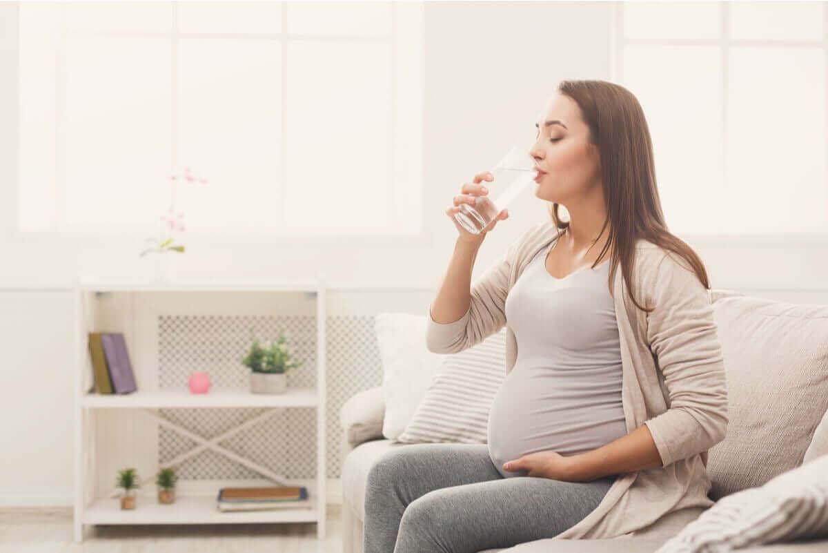 Gravid kvinne som drikker vann