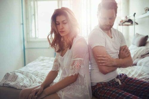 Et par som sitter på sengen med ryggen til hverandre