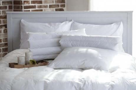 mange puter som ligger på en stor madrass