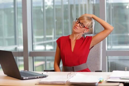 En sliten kvinne på et kontor