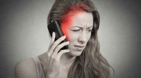En kvinne med hodepine som holder mobilen