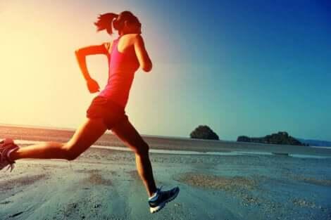 En kvinne som løper på stranden.