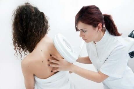 En kvinne som sjekker føflekkene sine hos en profesjonell