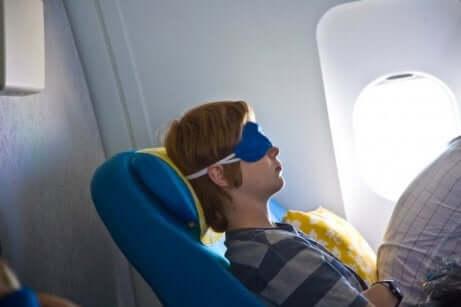 En person som sover på et fly