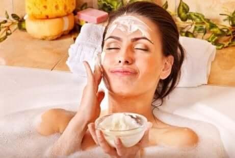 en kvinne som påfører ansiktsmaske i et badekar