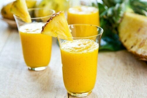 To glass med smoothie av ananas og mango