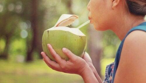 Jente som koser seg med kokosnøttvann.