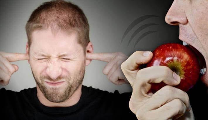 En mann irritert av noen som biter et eple som synger med lave serotoninnivåer