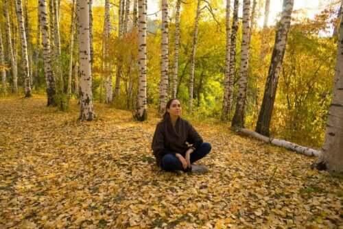 En kvinne som sitter i skogen