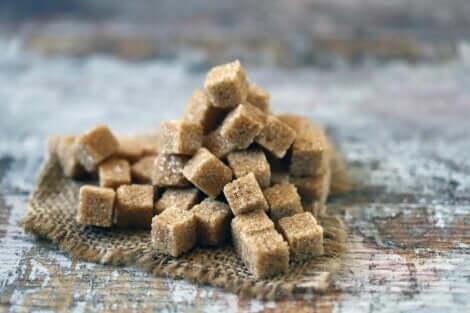 Å konsumere sukker: Brune sukkerbiter.