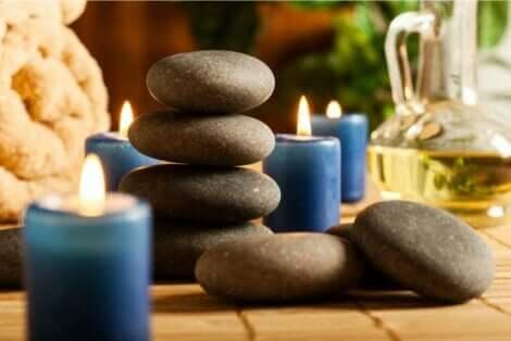 En haug med varme steiner omgitt av små blå lys, badehåndklær og en flaske olje.