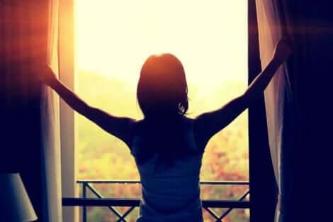 En kvinne som åpner gardinene på en solskinnsdag.