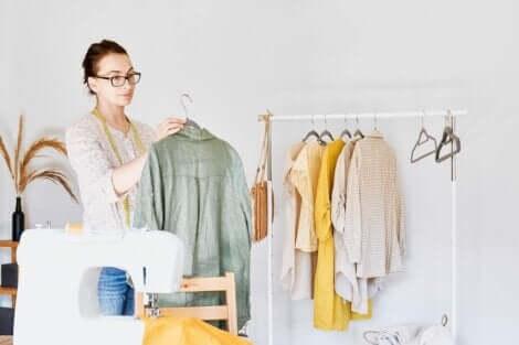 En kvinne som henger klær på et stativ, med en symaskin i forgrunnen.