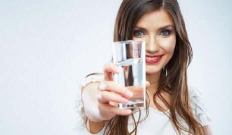 En kvinne som holder et glass vann