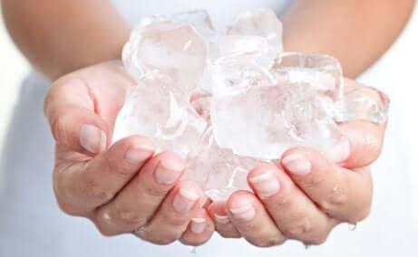 En kvinne som holder isbiter i hendene