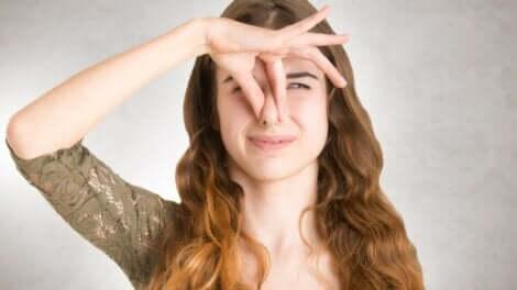 En kvinne som holder seg for nesen på grunn av en ubehagelig lukt.