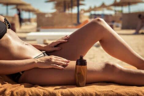 En kvinne som legger seg ut på stranden med en flaske olje ved siden av seg.