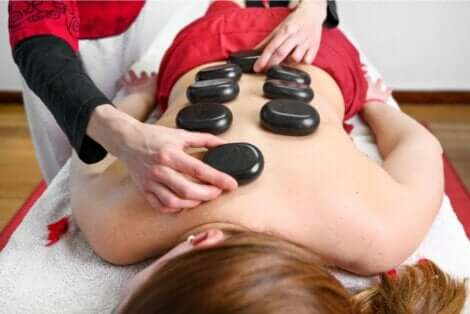 En kvinne som ligger på en massasjeseng med varme steiner på ryggen.