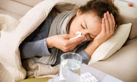 En kvinne som ligger på sofaen og er syk