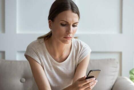 En kvinne som ser trist på mobiltelefonen sin.