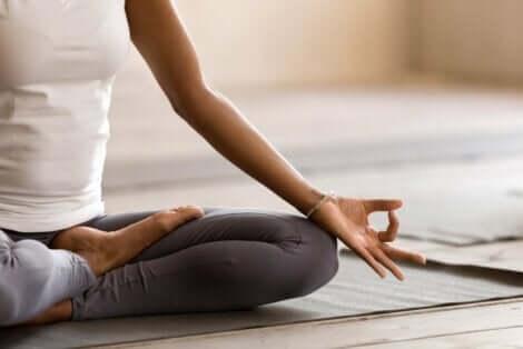 En kvinne som sitter på gulvet mens hun mediterer.