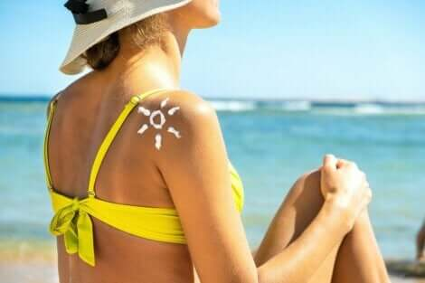 En kvinne som sitter på stranden med en sol laget av solkrem på skulderen.