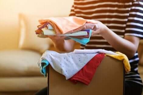 En kvinne som sorterer gjennom en eske med donerte klær.