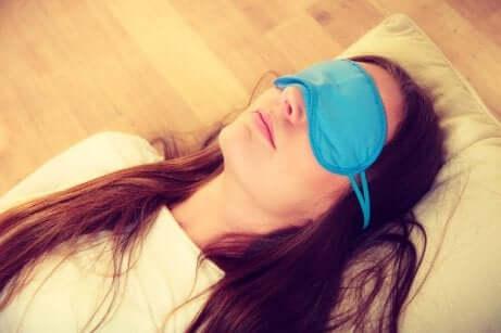 En kvinne som sover med sovemaske