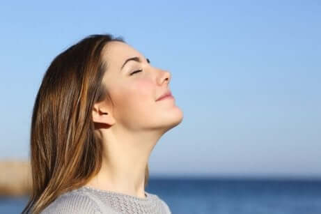 En kvinne som står med ansiktet i solen