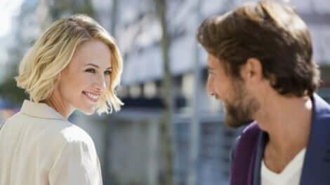 En mann og en kvinne som smiler til hverandre på gaten.