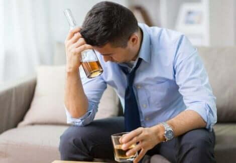 En mann som drikker alkohol og føler seg stresset.