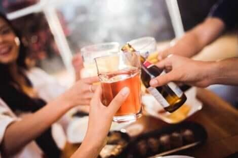 Venner som skåler med alkohol i baren.