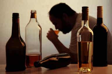 En mann som drikker et glass alkohol, omgitt av forskjellige flasker